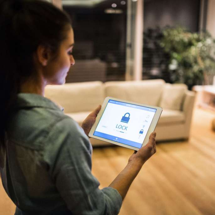 An unrecognizable woman holding a tablet with smart home control system.